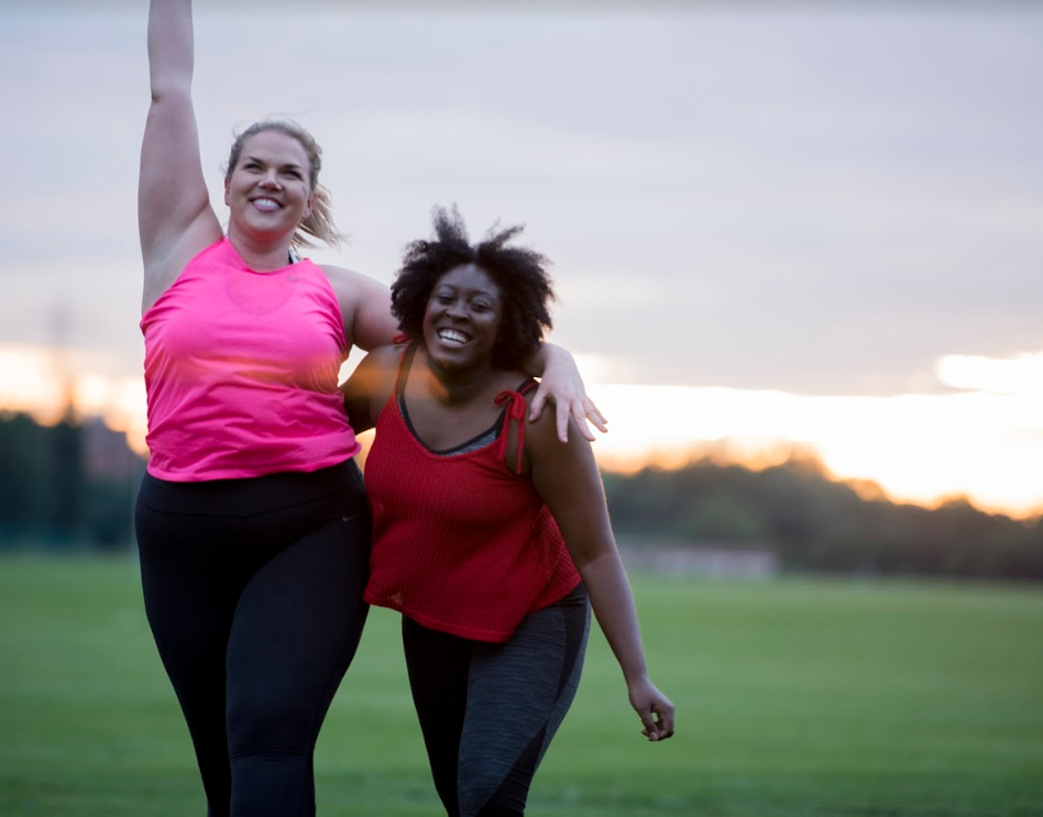 Two women looking triumphant that they've just completed a run. The woman on the left is wearing a pink t-shirt and has her arm in the arm. The other is wearing a red top and is leaning forwards slightly. Their arms are around each other.