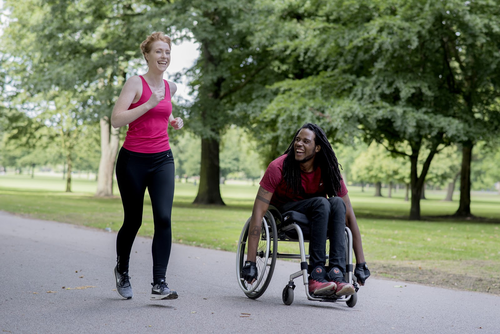 A woman in a pink t-shirt running alongside a man in a wheelchair through a park. Both are laughing.